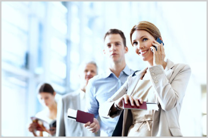 A pretty businesswoman talking on her cellphone while waiting in a queue at an airport